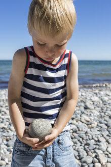 Portrait of a blond boy carrying stone on beach - OJF000133