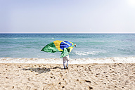 Little boy running with Brazilian flag on a beach - VABF000364