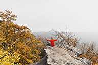 Germany, Rhineland Palatinate, Palatinate Forest, woman practising yoga on Drachenfels in autumn - GWF004644