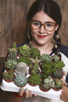 Hipster young woman with tray cacti and succulents - RTBF000005