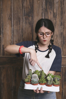 Hipster young woman with tray cacti and succulents, barbed - RTBF000008