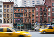 USA, New York City, Manhattan, yellow cabs driving in front of old brick houses - HSI000417