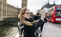 UK, London, young woman taking a selfie on Westminster Bridge - MGOF001544