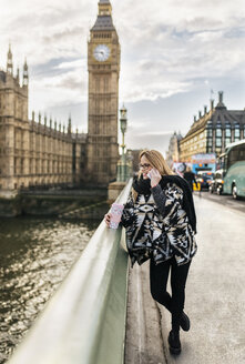 UK, London, young woman talking on phone on Westminster Bridge - MGOF001547