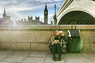 UK, London, young woman listening music near Westminster Bridge - MGOF001553