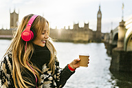 UK, London, young woman listening music and drinking coffee near Westminster Bridge - MGOF001556