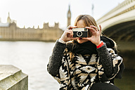UK, London, young woman taking a picture near Westminster Bridge - MGOF001559