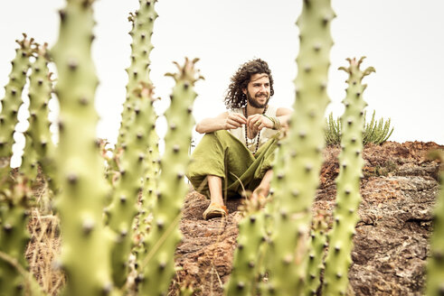 Man sitting on rock behind cacti, smiling - BMAF000107