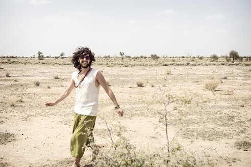 Smiling man with sunglasses walking alone in the desert - BMAF000116