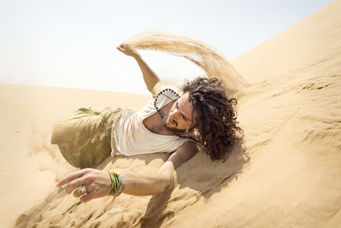 Man rolling down sand dune - BMAF000137