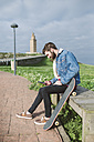 Spain, A Coruna, young man with longboard using smartphone - RAEF000944