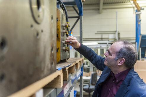 Man examining machine block in storehouse - DIGF000051