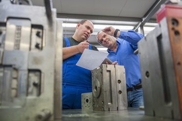 Two men discussing a metal workpiece - DIGF000069