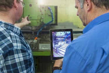 Two men in factory with digital tablet at a machine - DIGF000072