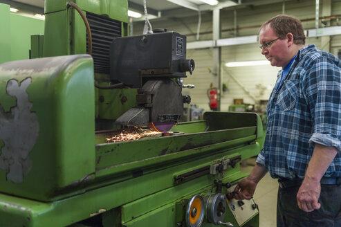 Man operating grinding machine - DIGF000078