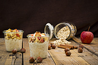 Glasses of overnight oats with sliced apple, hazelnuts and cinnamon - LVF004657