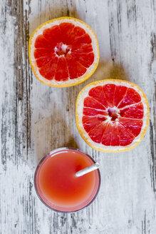 Sliced grapefruit and glass of grapefruit juice on wood - SARF002652