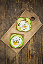 Wholemeal bread slices with sliced avocado and poached eggs on wooden board - LVF004669