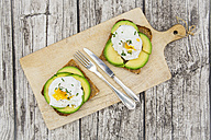 Wholemeal bread slices with sliced avocado and poached eggs on wooden board - LVF004672