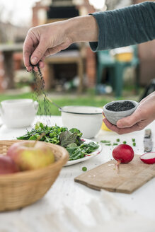 Hand preparing salad seasoning with black sesame - DEGF000748