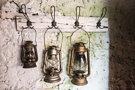 Old vintage storm lamps on painted stone wall - DEGF000757