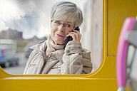 Portrait of smiling senior woman telephoning with smartphone looking inside a telephone booth - FR000400