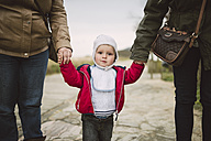 Portrait of toddler walking hand in hand with two women - RAEF000946
