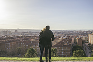 Spain, Madrid, back view of young couple in love on a hill looking to the city - ABZF000290