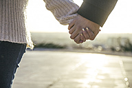 Young couple holding hands at backlight, close-up - ABZF000293