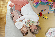 Pregnant mother and little daughter cuddling on carpet at home - MFF002902