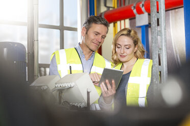 Colleagues wearing reflective vests sharing digital tablet in industrial plant - FKF001731