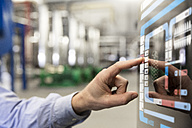 Man using touchscreen device in industrial plant - FKF001734