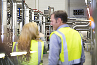Colleagues wearing reflective vests talking in industrial plant - FKF001737