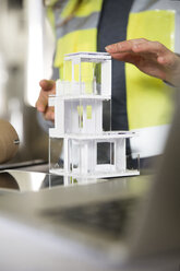 Close-up of woman wearing reflective vest with architectural model - FKF001740