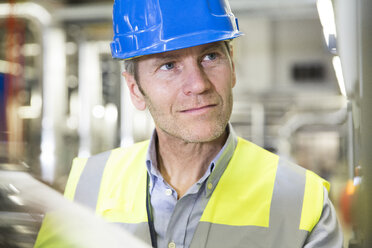 Man wearing reflective vest looking around in industrial plant - FKF001743