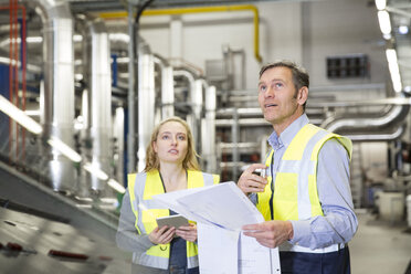 Colleagues wearing reflective holding plan in industrial plant - FKF001749