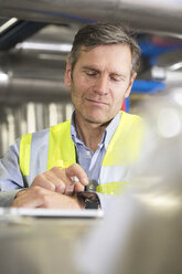 Man using smartwatch in industrial plant - FKF001755