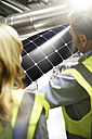 Colleagues wearing reflective vests examining innovative solar panel - FKF001767