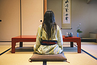 Japan, Uji, back view of woman wearing yukata drinking tea in a traditional Japanese room - GEMF000803