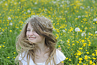 Portrait of smiling girl with dandelion seed on her hair - CRF002747