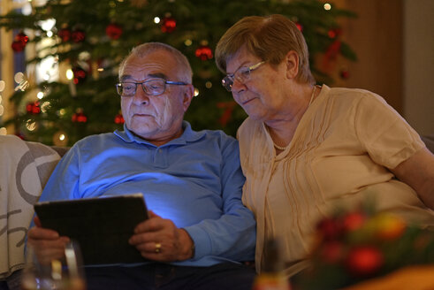Senior couple looking at digital tablet  in front of Christmas tree - LBF001420