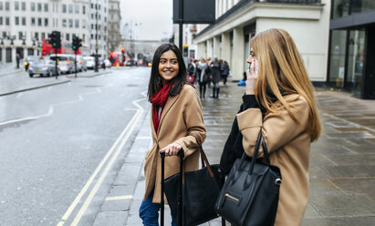 UK, London, Two friends exploring the city, using smart phone - MGOF001566