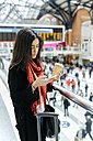 UK, London, Young woman using mobile phone at train station - MGO001569