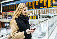 UK, London, Young woman using mobile phone at train station - MGO001572