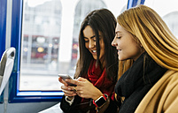 UK, London, Two young women using smart phone on the bus - MGOF001575