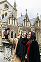 UK, London, Two friends exploring the city, photographing selves in front of Southwark Cathedral - MGOF001578