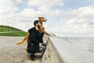 Man and his dog looking at the sea - MGOF001605