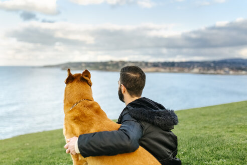 Spain, Gijon, back view of a man sitting on a meadow with his dog looking at distance - MGOF001608
