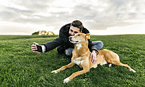 Man taking a selfie with his dog on a meadow - MGOF001611