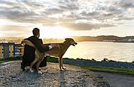 Spain, Gijon, man and his dog at evening twilight - MGOF001620